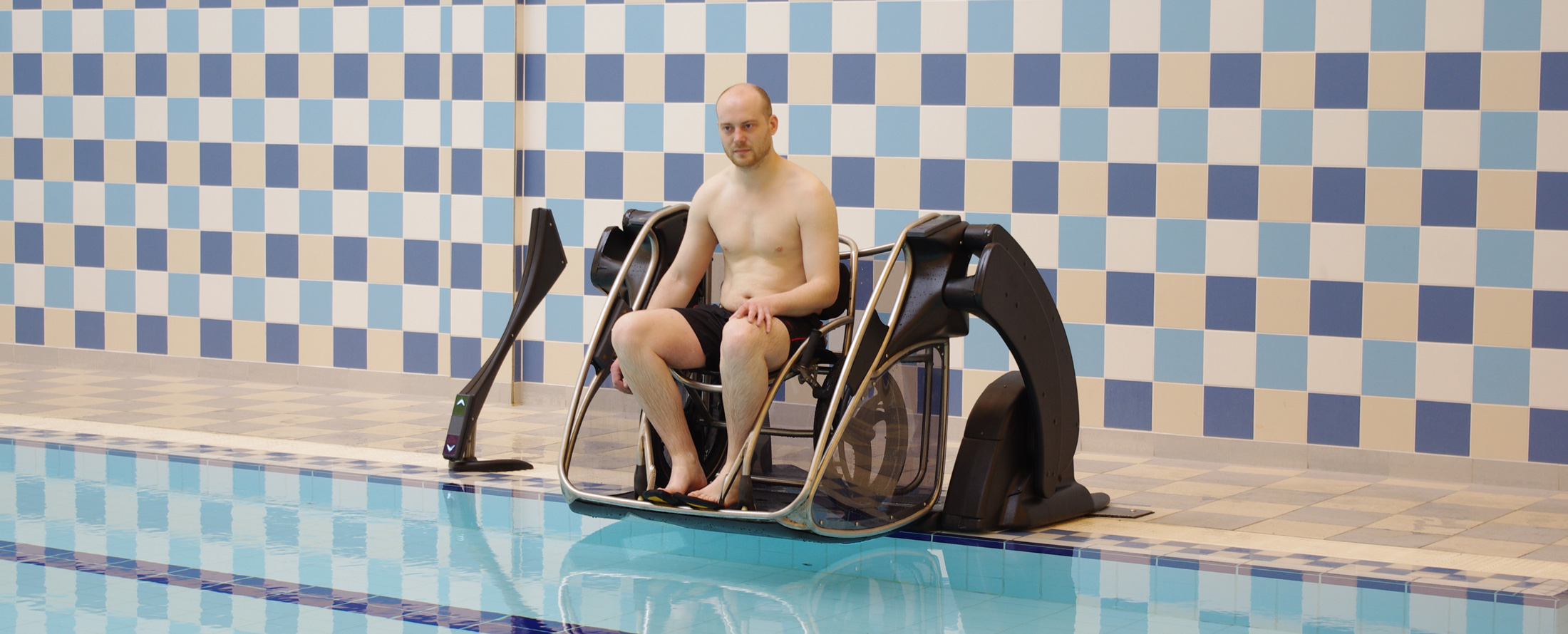 Pool lift with male wheelchair user present on platform.